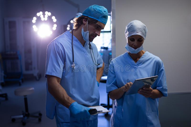 Surgeons discussing over digital tablet at hospital stock photos