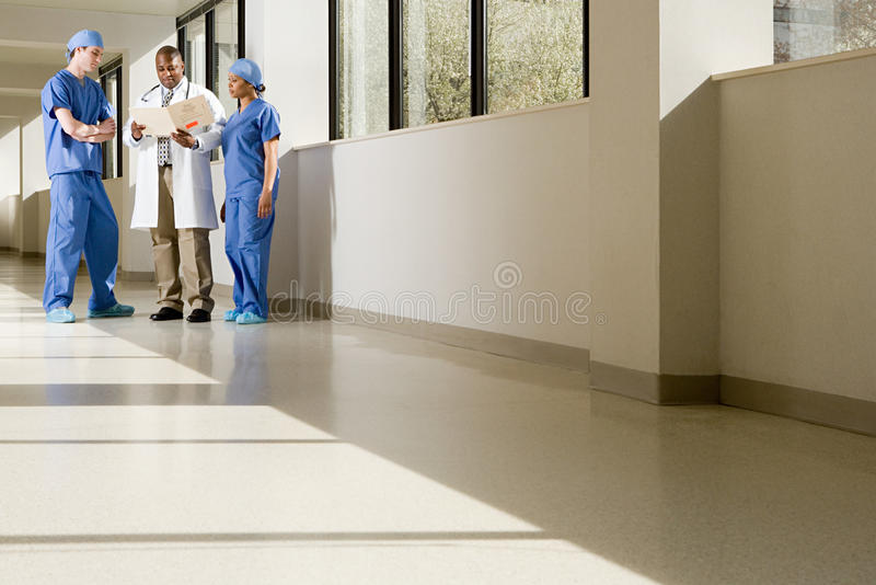 Surgeons and doctor looking at file stock photo