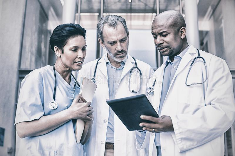 Surgeons and nurse having discussion on digital tablet stock photos