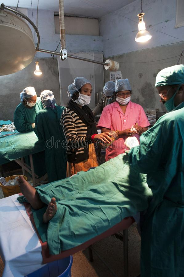 Surgeons and nurses conduct a tubal ligation on a young woman in Bihar, India.  stock photography