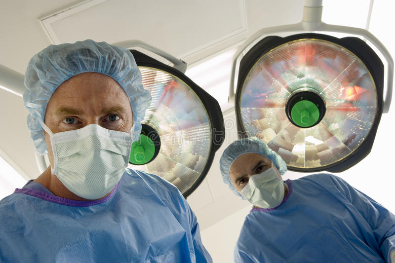 Surgeons in surgical masks standing in operating theatre, low angle view, personal perspective stock image