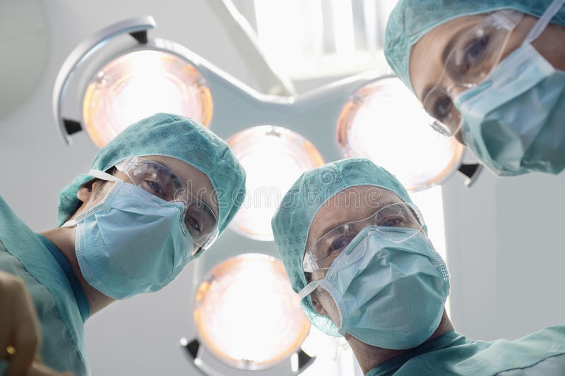 Surgeons Under Surgery Lights In Operating Theatre. Low angle view of three surgeons under surgery lights in operating theatre stock images