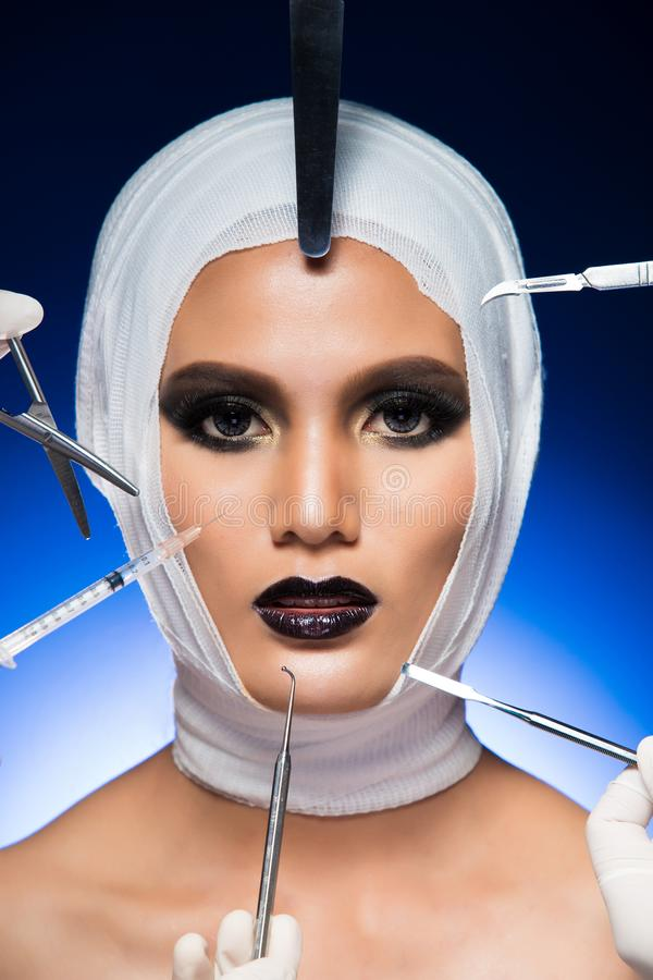 Surgery Patient bandage equipment around head. Beauty Aesthetic Plastic Surgery Patient with bandage, surgical tools, equipment around head. Studio Lighting stock photography
