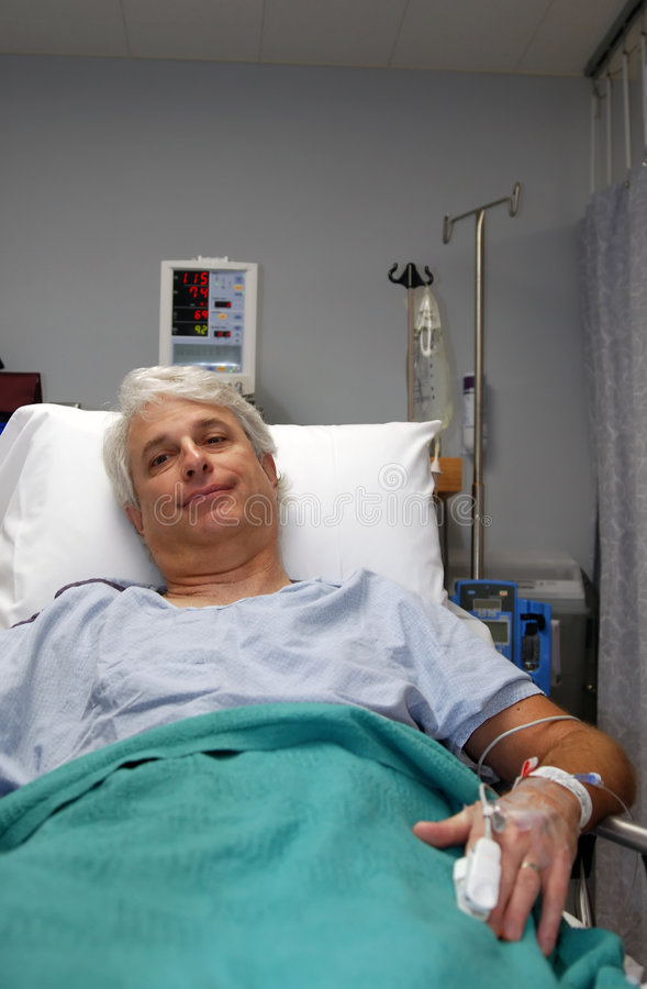 Surgery recovery. Man in hospital bed recovering from surgery with IV and heart rate monitor and blood pressure stock images