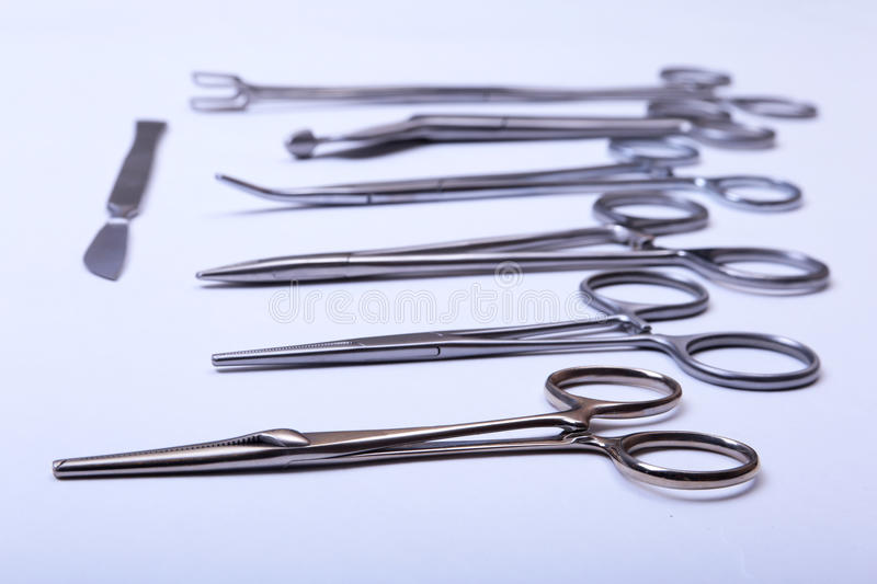 Surgical instruments and tools including scalpels, forceps tweezers arranged on a table for surgery. Surgical instruments and tools including scalpels, forceps royalty free stock image