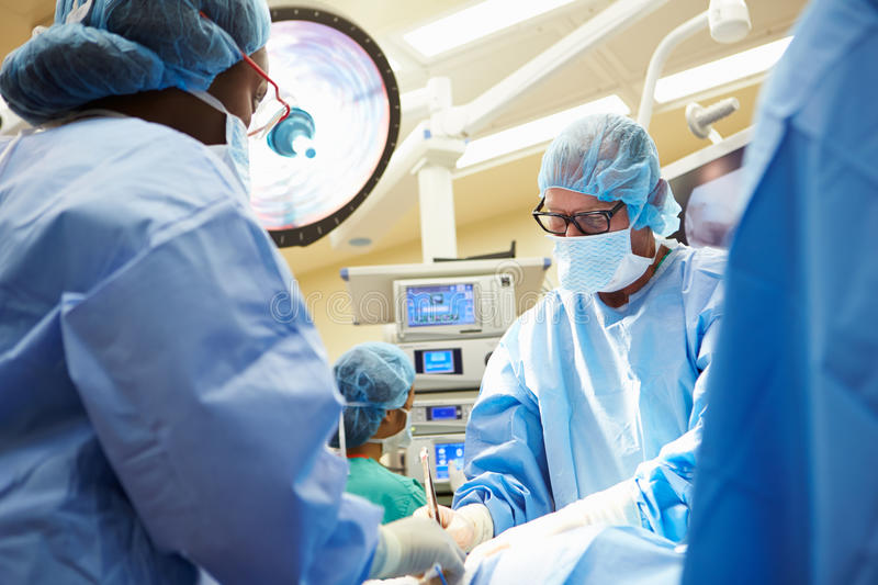 Surgical Team Working In Operating Theatre royalty free stock images
