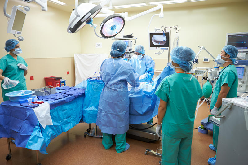 Surgical Team Working In Operating Theatre. Wearing Protective Clothing Using Medical Equipment stock photos