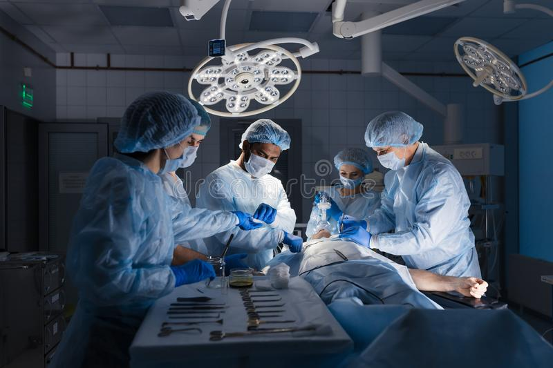 Surgical tools lying on table with nurse near and surgeons at background. royalty free stock images