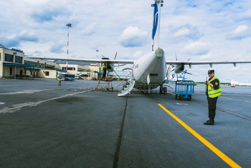 Surgut, Rusland - Juni 27, 2017: Veiligheidsagent dichtbij de vliegtuigen royalty-vrije stock fotografie