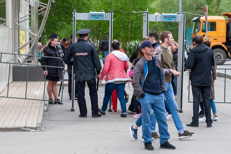 A police officer controls the passage of citizens through the metal detector frame, before entering the festive event. Surgut, Russia, 06.12.2019: A police stock photo