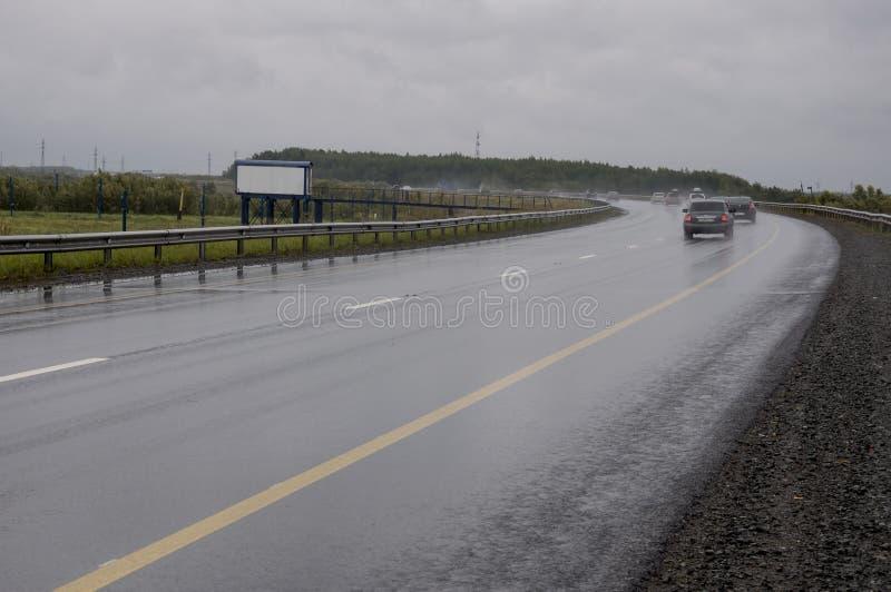 Surgut, YaNAO, al norte de Rusia 1 de septiembre de 2017 Puente anaranjado grande con los coches en él Carretera de asfalto Mún t imagen de archivo libre de regalías