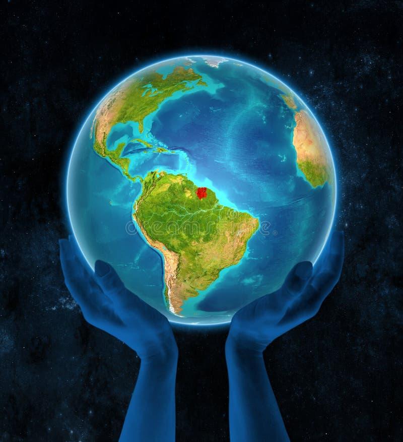 Surinam på jord i händer royaltyfria bilder