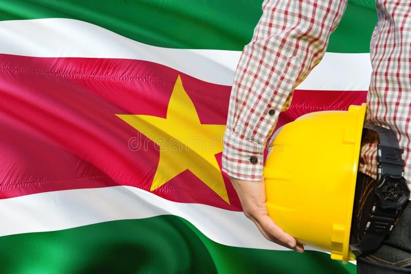 Surinamese inżynier trzyma żółtego zbawczego hełm z machać Suriname chorągwianego tło Budowy i budynku poj?cie obrazy royalty free
