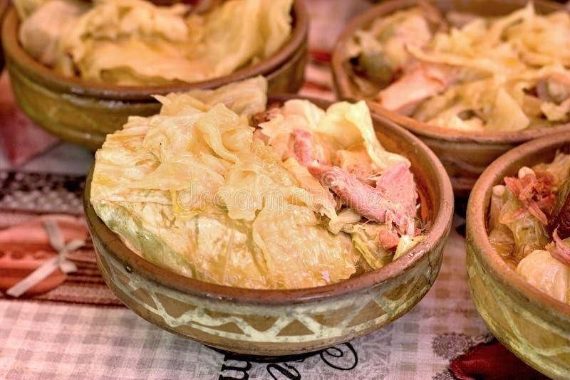 Surkål - kål med den rökte knogen, skinkahock, grisköttknä, grisköttskuldra i jordnära bunke fotografering för bildbyråer