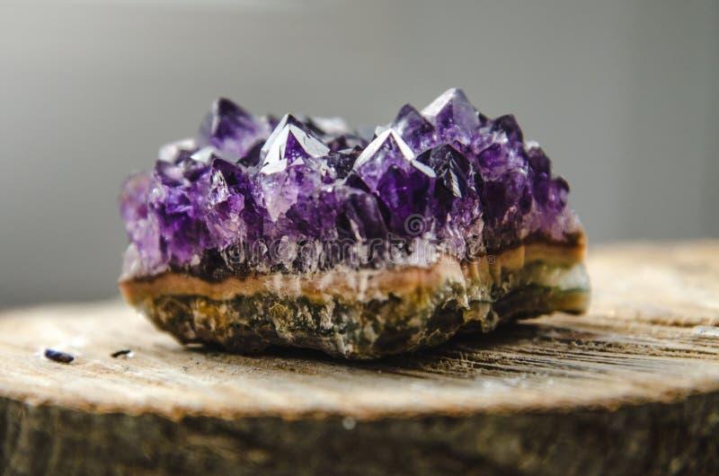Surowa ametyst skała z odbiciem na naturalnym drewnianym krystalicznym ametist fotografia royalty free