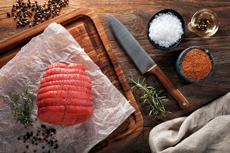 Surowa bezkostna cielęciny pieczeń na białym kucharstwo papierowym i drewnianym rozcięcie stole Dekorujący z ziele, pikantność i  zdjęcie stock