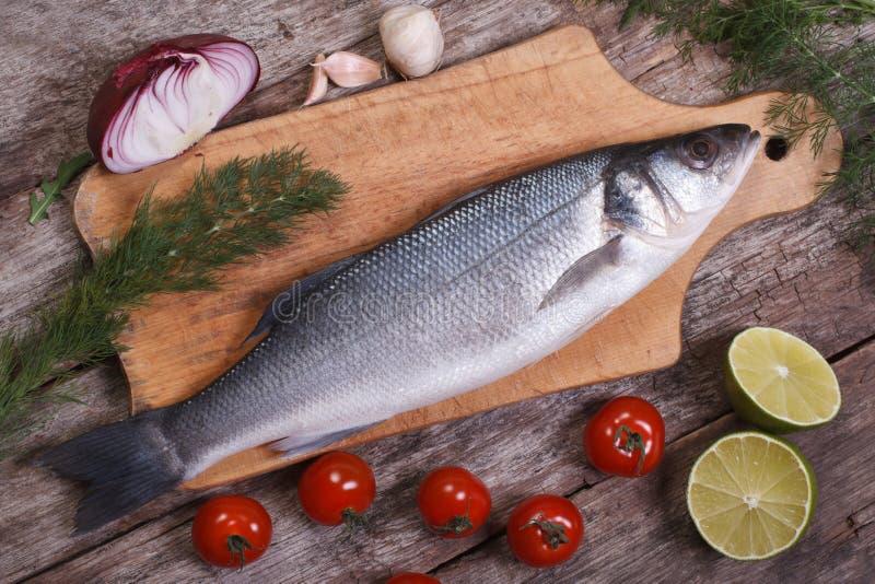 Surowa dennego basu ryba na tnącej desce z warzywo odgórnym widokiem fotografia stock