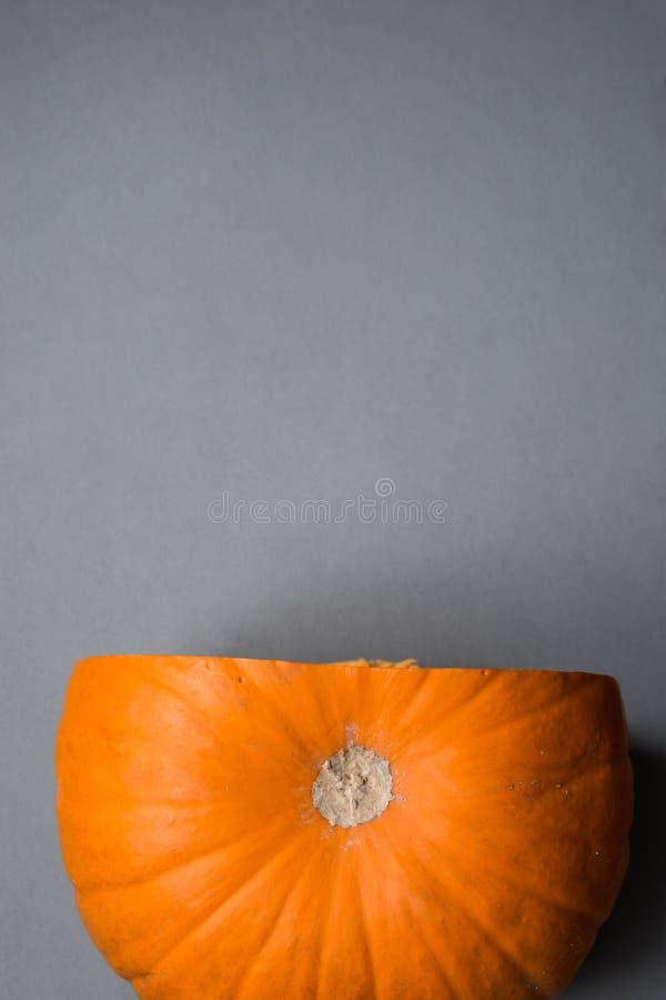 Surowa Jaskrawa Pomarańczowa Heirloom bania z Odcinał kawałek na Popielatym Kamiennym tle Dziękczynienie spadku jesień Halloween fotografia stock