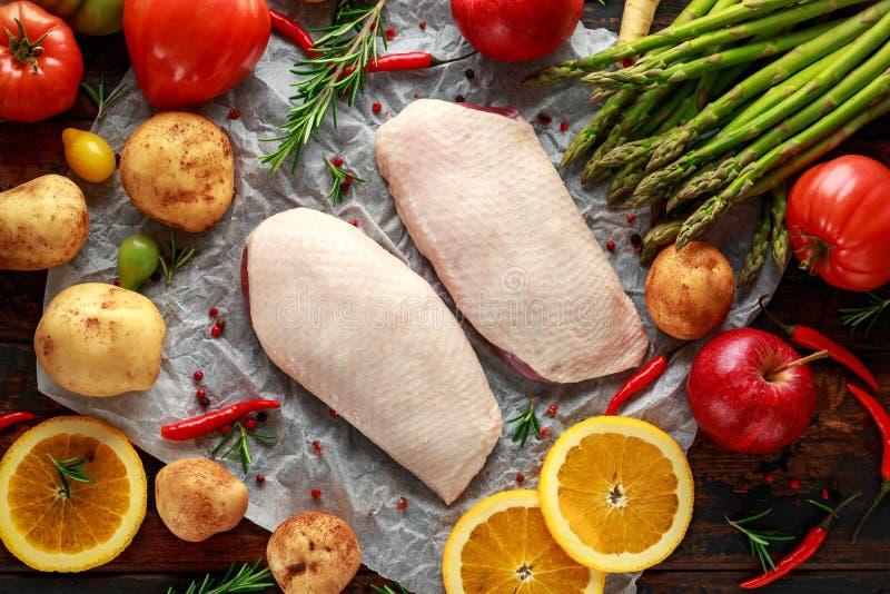 Surowa kaczki pierś na pieczenie papierze z rozmaitością warzywa fotografia stock