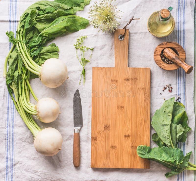 Surowa młoda rzepa z zieleniami na lekkim kuchennym stole z pustą tnącą deską i nożem, odgórny widok Zdrowy jarski czysty łasowan zdjęcie stock