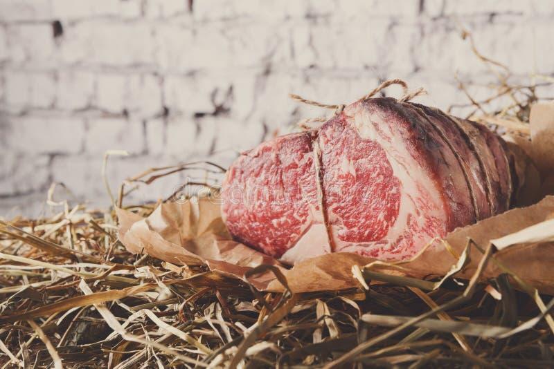 Surowa starzejąca się pierwszorzędna czarna Angus wołowina w rzemiosła papper na słomie zdjęcie stock