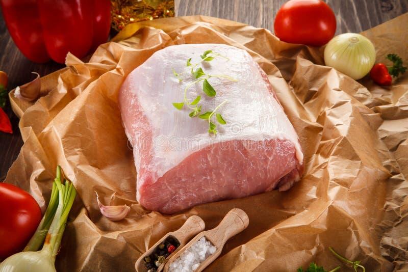 Surowa wieprzowina na tnącej desce i warzywach zdjęcie stock