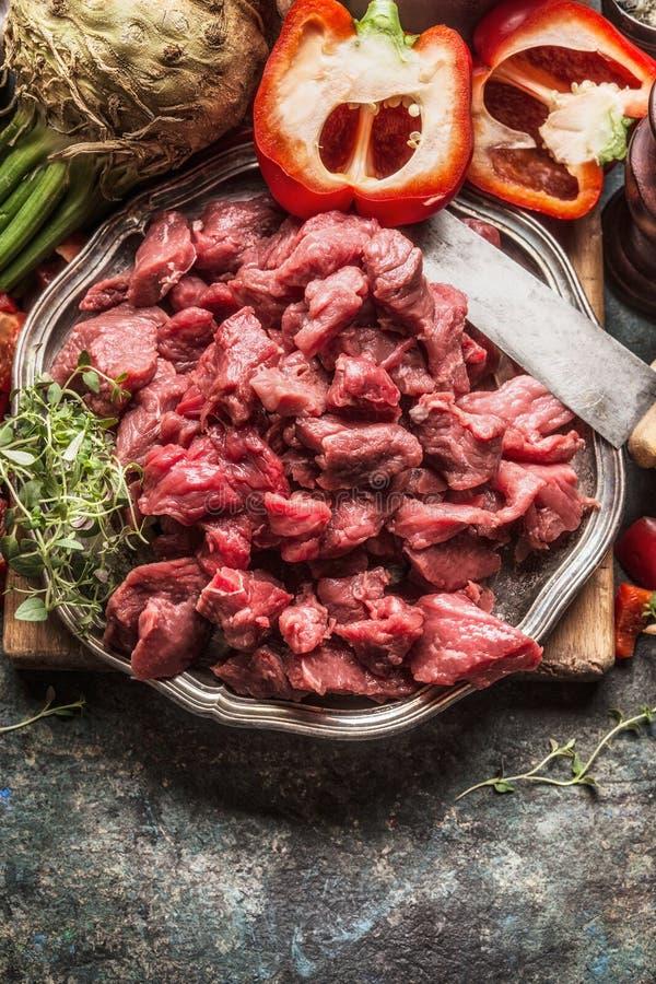 Surowa wołowina siekający warzywo składnik, kuchenny nóż i kucharstwo mięśni, puszkujemy Gulaszu lub goulash przygotowanie obraz royalty free