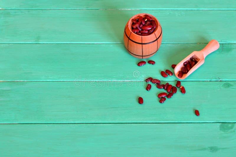 Surowe czerwone fasole w małej baryłce i drewnianej miarce na zielonym tle fotografia royalty free