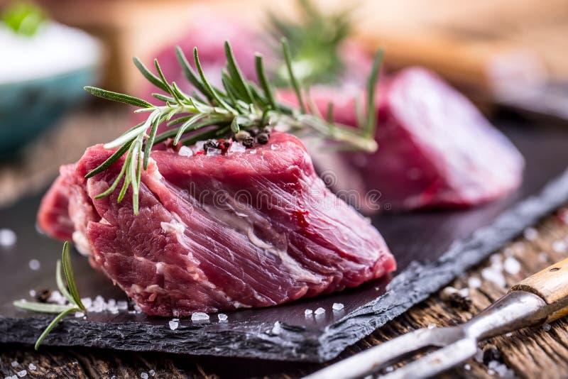 surowe mięso wołowiny Surowy wołowiny tenderloin stek na tnącej desce z rozmarynu pieprzu solą w inny pozycje zdjęcie royalty free