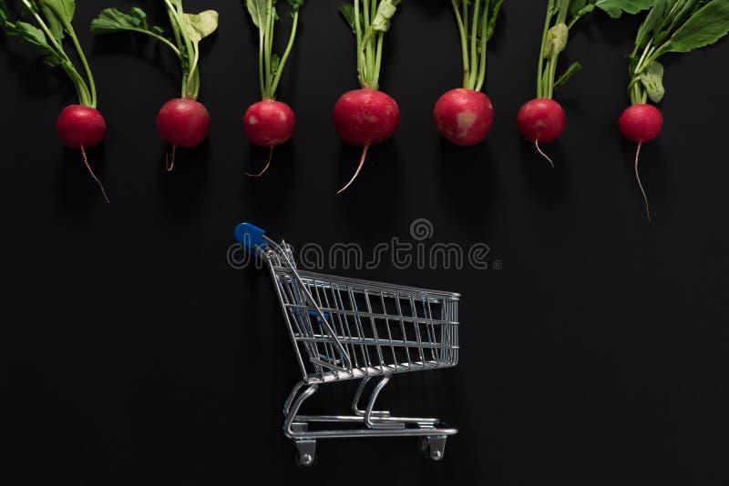 Surowe rzodkwie i wózek na zakupy fotografia royalty free