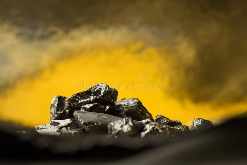 Surowe węglowe bryłki na złotym lekkim tle z ciemnym plamy przedpolem obrazy stock
