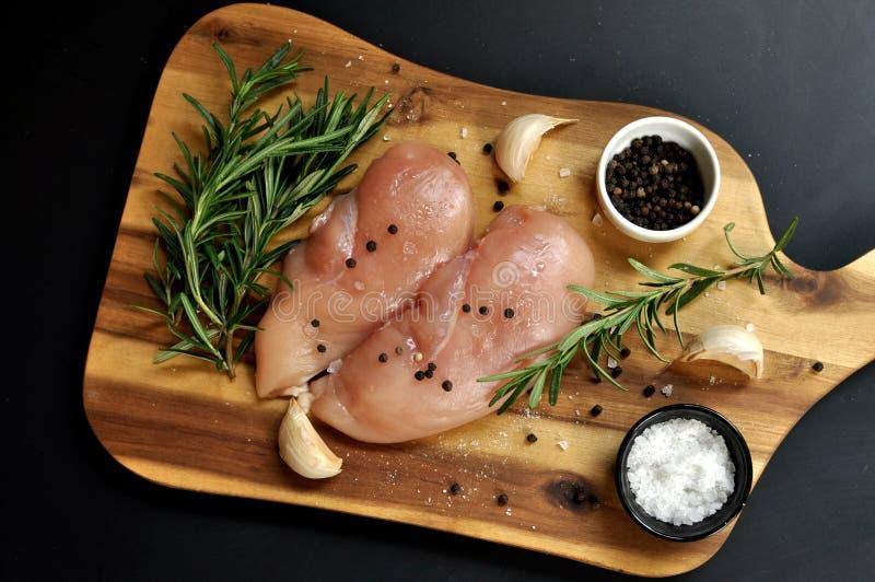 Surowego świeżego uncooked kurczak piersi mięsa polędwicowy naczynie z rozmarynami, pieprzem, solą i czosnkiem na, drewnianej des obrazy stock