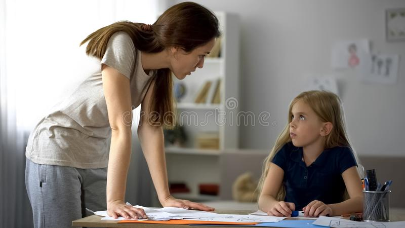 Surowego macierzystego krytykowania mała córka dla rysunków, zaakcentowany dzieciństwo fotografia stock