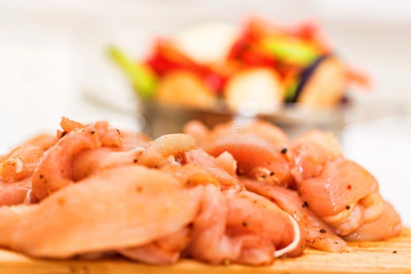 Surowego spiced kurczaka polędwicowi i świezi warzywa obraz stock
