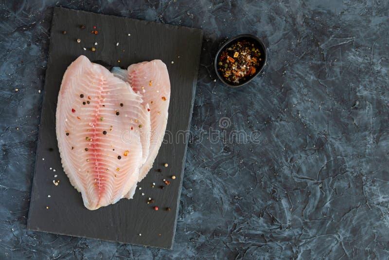 Surowego tilapia rybi polędwicowy z macierzanką, pieprzy pikantność gotowe dla gotować Odbitkowa przestrzeń, odgórny widok zdjęcie stock