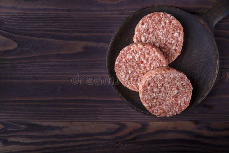 Surowej minced wołowiny hamburgeru mięśni cutlets na ciemnym drewnianym tle obraz stock