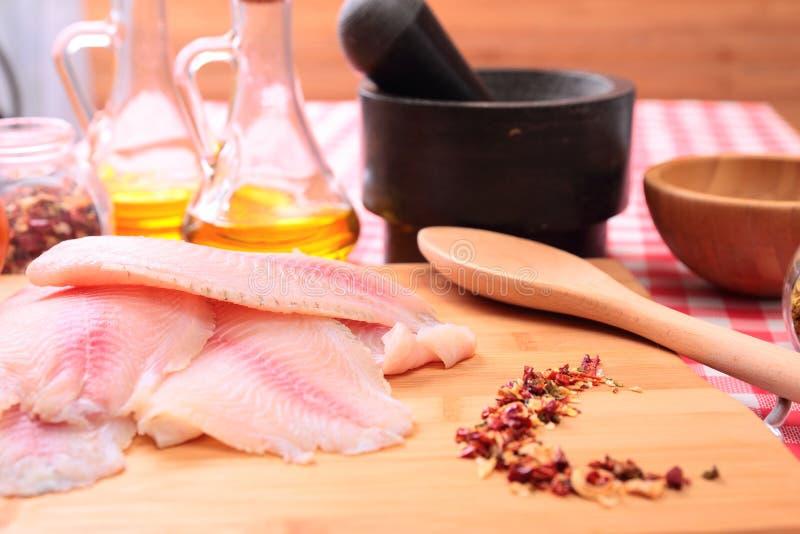 Surowej ryba tilapia na tnącej desce i pikantność obraz stock