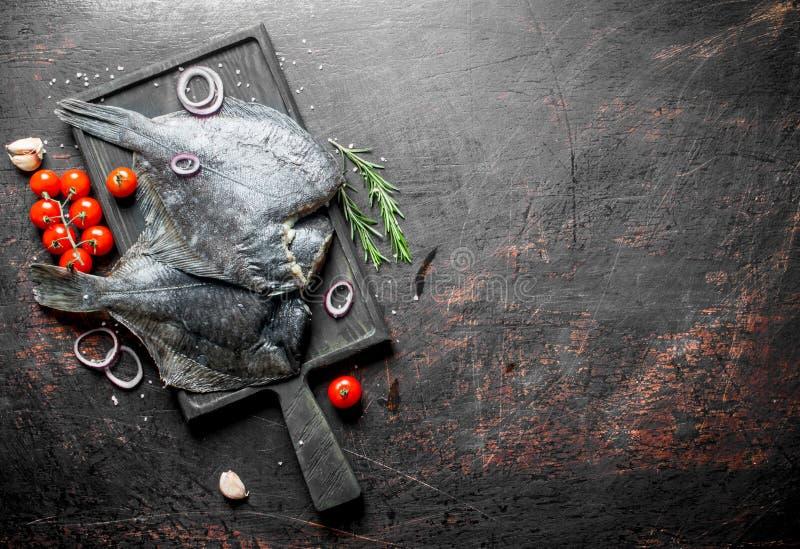 Surowej ryby flądra na tnącej desce z czereśniowymi pomidorami i pokrojonymi cebulami obrazy stock