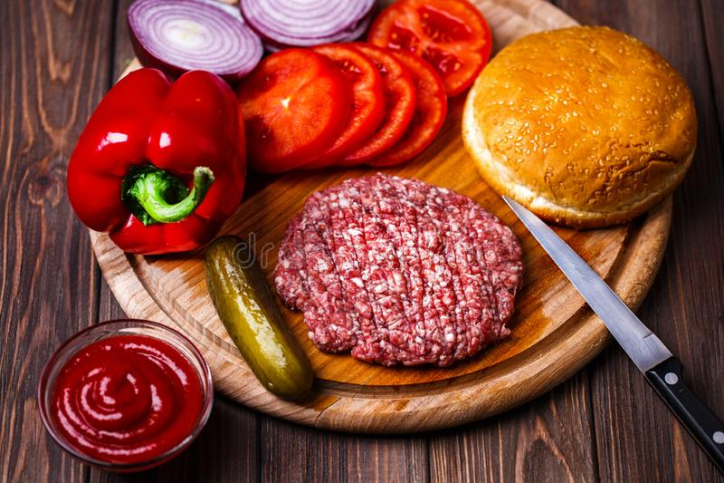 Surowej Zmielonej wo?owiny hamburgeru stku mi??ni cutlets z podpraw?, serem, pomidorami, sa?atk? i babeczk? na rocznik drewnianyc obraz royalty free