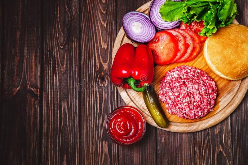 Surowej Zmielonej wo?owiny hamburgeru stku mi??ni cutlets z podpraw?, serem, pomidorami, sa?atk? i babeczk? na rocznik drewnianyc zdjęcie stock
