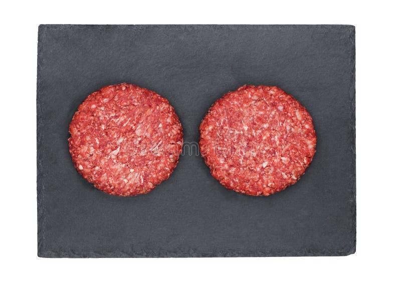 Surowi świezi wołowina hamburgery na kamienia talerzu fotografia royalty free