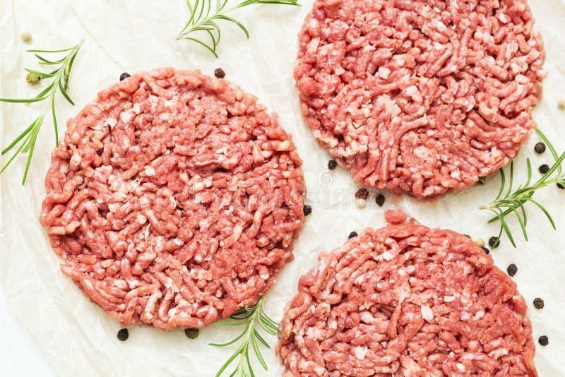 Surowi hamburgery bez sadła od organicznie wołowiny na białym drewnianym tle z pikantność Posilny jedzenie Odgórny widok obrazy stock