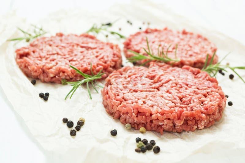 Surowi hamburgery bez sadła od organicznie wołowiny na białym drewnianym tle z pikantność Wysokiej jakości minced mięso obraz stock