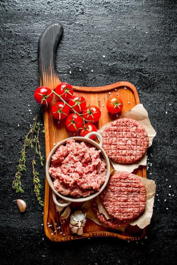 Surowi hamburgery i ziemi wo?owina z pomidorami, czosnk?w cloves i macierzank?, obraz royalty free