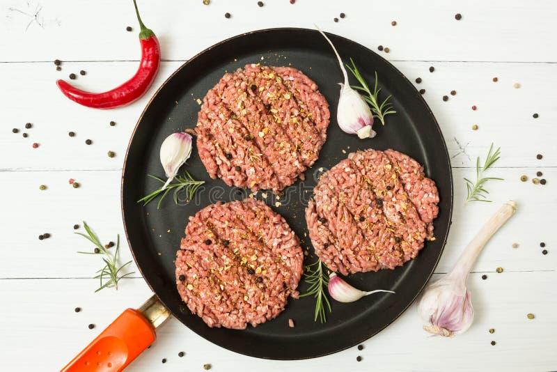 Surowi hamburgery - minced mięso od organicznie mięsa z cloves czosnek, gorącego chili pieprz i rozmaryny w smaży niecce na bielu obrazy royalty free