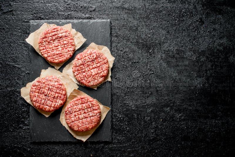 Surowi hamburgery na papierze zdjęcia royalty free