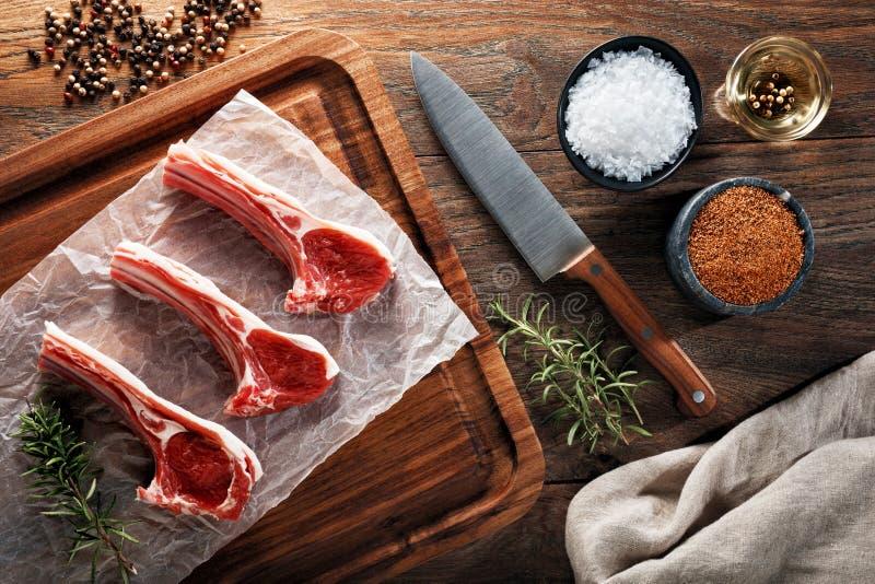Surowi jagnięcy ziobro kotleciki na białym kucharstwo papierowym i drewnianym rozcięcie stole zdjęcia stock