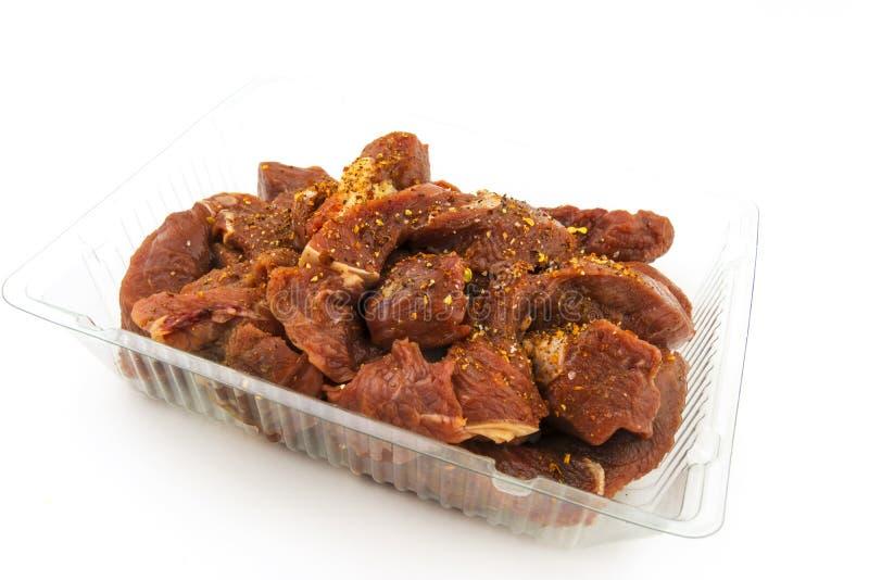 Surowi kawałki wołowina, goulash w plastikowej tacy, kropiącej z pikantność Na białym tle zdjęcia stock