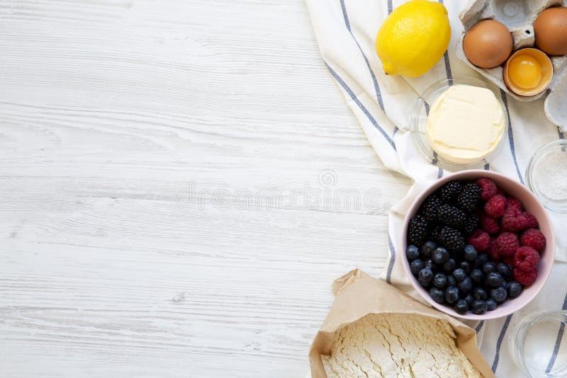 Surowi składniki: jagody, mąka, jajka, masło, cytryna, woda, sól dla kulinarnego jagodowego kulebiaka na białym drewnianym tle, o zdjęcia royalty free