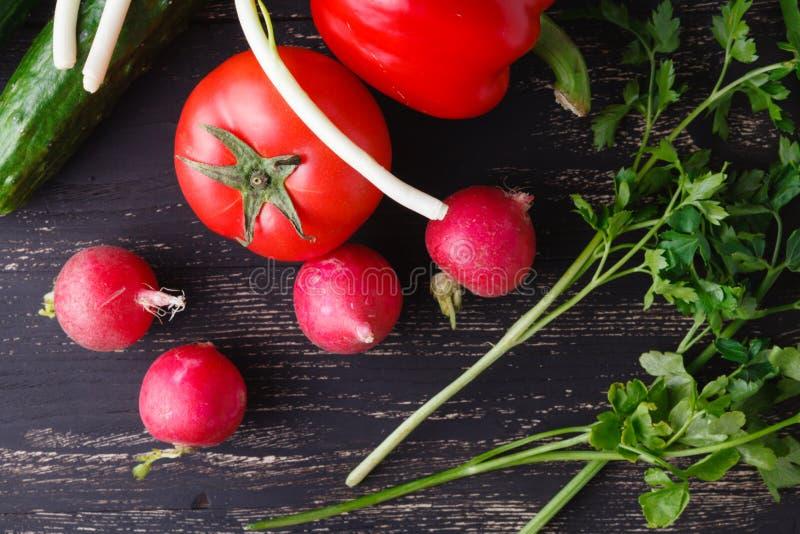 Surowi składniki - kalafior, grula, zucchini, marchewka, cebula, pieprz, gotuje piec warzywa Na ciemnym drewnianym tle zdjęcie royalty free